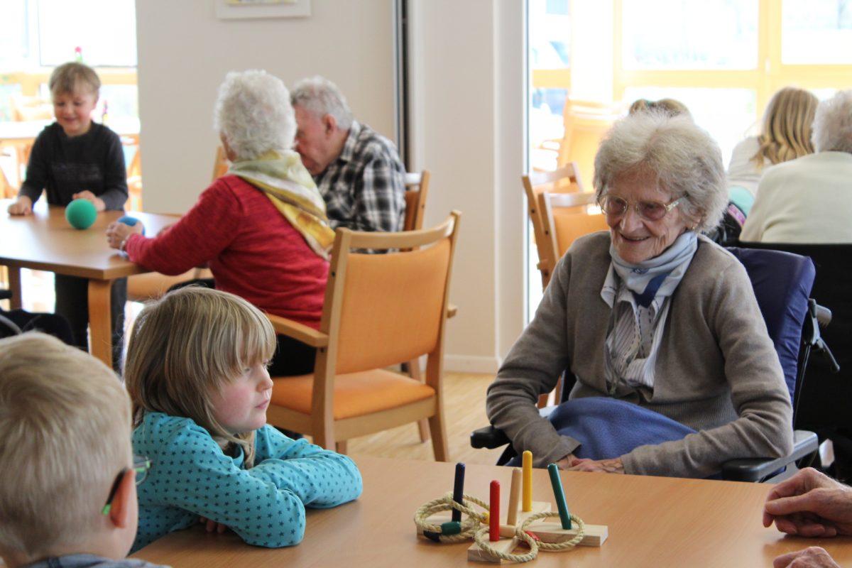 Kinder und Senioren spielen zusammen